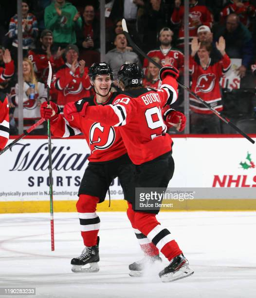 Jesper Boqvist of the New Jersey Devils celebrates his first NHL goal during the first period against the Minnesota Wild and is joined by Jack Hughes...