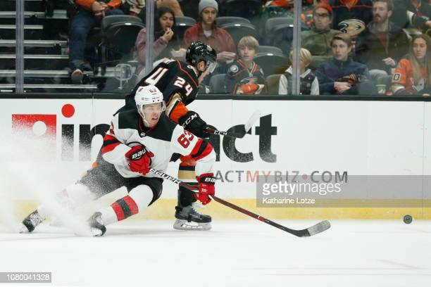 Jesper Bratt of the New Jersey Devils and Carter Rowney of the Anaheim Ducks fight for control of the puck at Honda Center on December 09 2018 in...