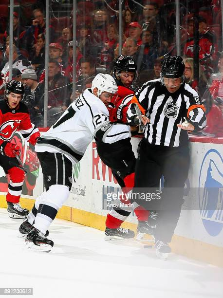 Jesper Bratt of the New Jersey Devils is checked into the boards by Alec Martinez of the Los Angeles Kings during the game at Prudential Center on...