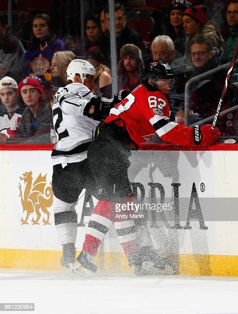 Jesper Bratt of the New Jersey Devils is checked into the boards by Marian Gaborik of the Los Angeles Kings during the game at Prudential Center on...