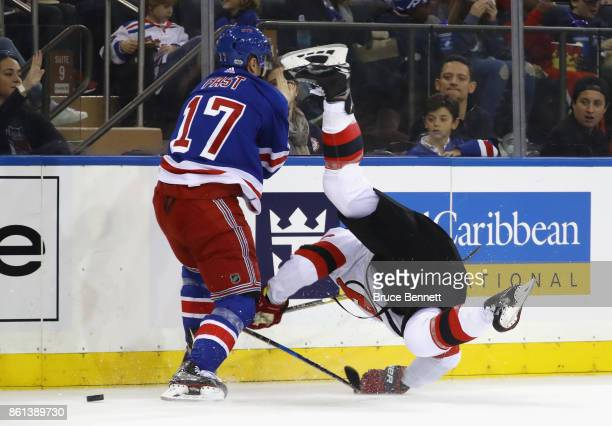 Jesper Fast of the New York Rangers checks Steven Santini of the New Jersey Devils during the first period at Madison Square Garden on October 14...