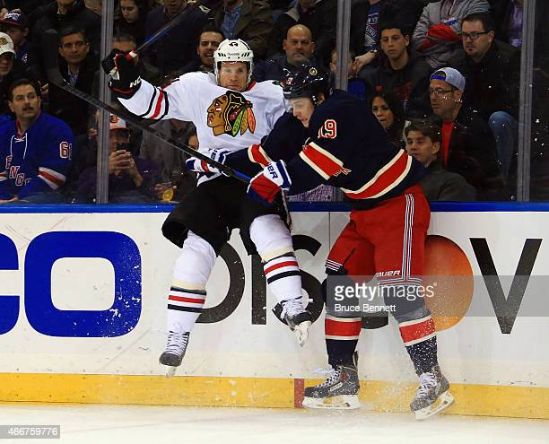 Jesper Fast of the New York Rangers hits Kimmo Timonen of the Chicago Blackhawks into the boards during the first period at Madison Square Garden on...