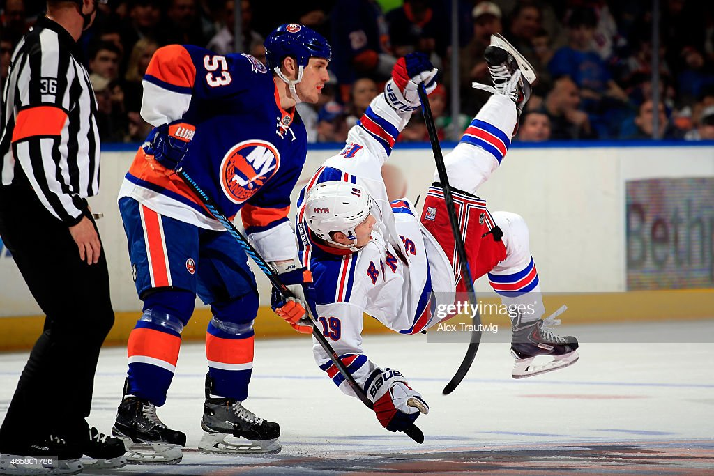 Jesper Fast #19 of the New York Rangers is tripped by Casey Cizikas #53 of the New York Islanders prior to a faceoff during a game at the Nassau Veterans Memorial Coliseum on March 10, 2015 in Uniondale, New York.