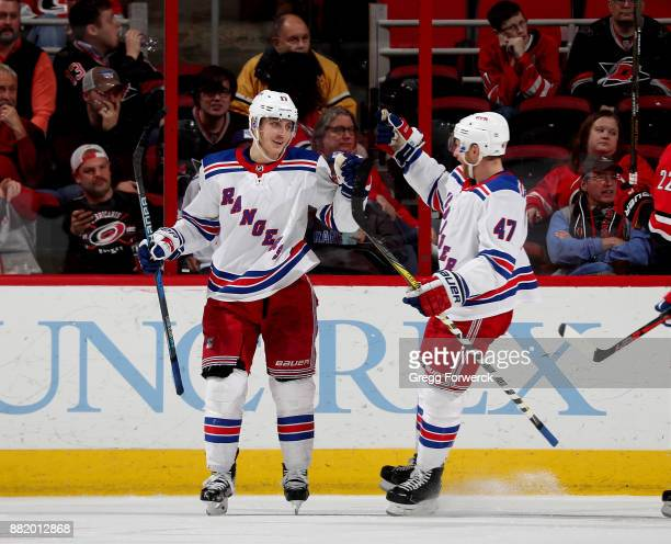 Jesper Fast of the New York Rangers scores a goal and celebrates with teammate Steven Kampfer during an NHL game against the Carolina Hurricanes on...
