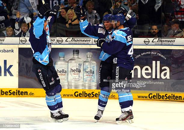 Jesper Jensen of Hamburg celebrate with his team mates after he scores his team's opening goal during the DEL match between Hamburg Freezers and...