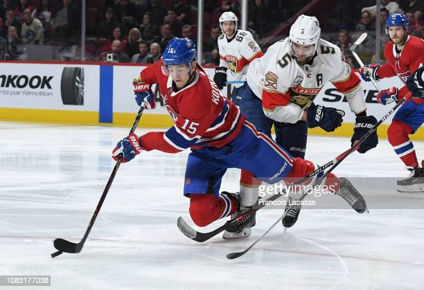 Jesperi Kotkaniemi of the Montreal Canadiens passes the puck against pressure from Aaron Ekblad of the Florida Panthers in the NHL game at the Bell...