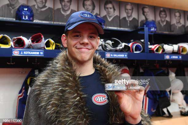 Jesperi Kotkaniemi of the Montreal Canadiens poses in the locker room with a puck after scoring his first NHL career goal while defeating the...
