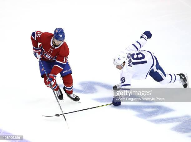 Jesperi Kotkaniemi of the Montreal Canadiens tries to keep the puck from Mitchell Marner of the Toronto Maple Leafs in the third period during an...
