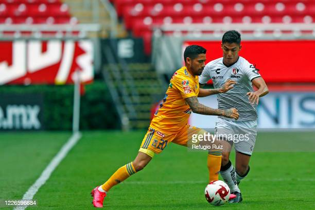 Jesús Angulo of Atlas fights for the ball with Javier Aquino of Tigres during the match between Atlas and Tigres UANL as part of the friendship...