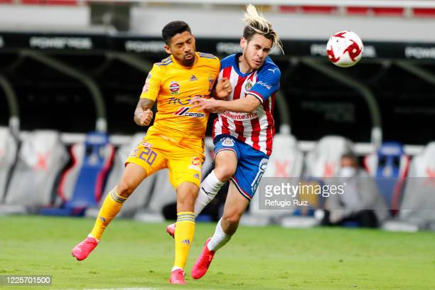 Jesús Angulo of Chivas fights for the ball with Javier Aquino of Tigres during the match between Chivas and Tigres UANL as part of the friendly...