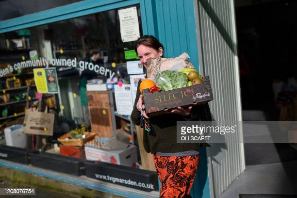 Jess Atkinson, a volunteer for the community owned grocery shop, The Village Green, leaves to deliver an emailed order from a local resident...