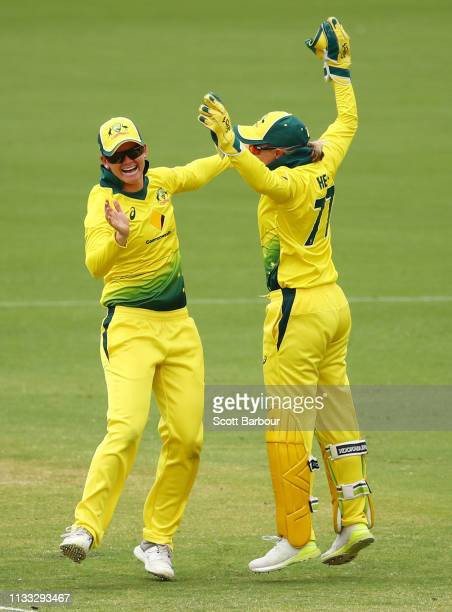 Jess Jonassen and Alyssa Healy of Australia celebrate after running out Amy Satterthwaite of New Zealand during game three of the One Day...