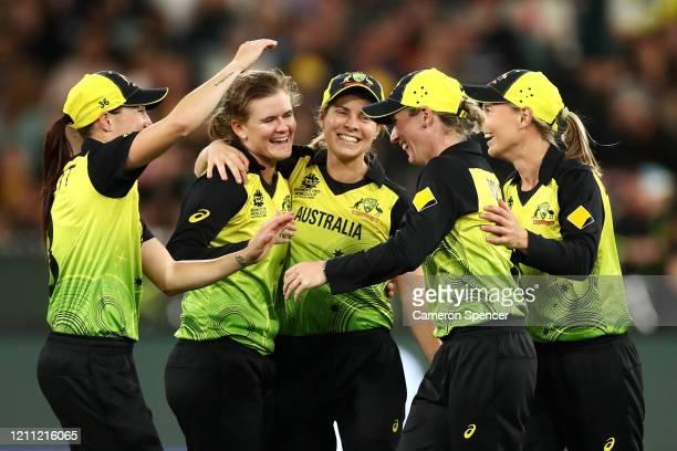 Jess Jonassen of Australia celebrates dismissing Radha Yadav of India with Beth Mooney of Australia after she caught her during the ICC Women's T20...