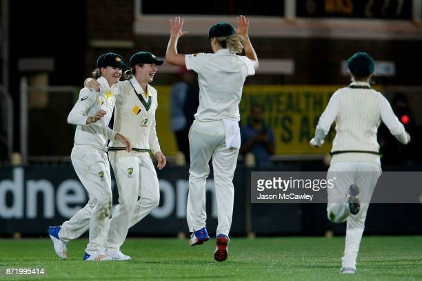 Jess Jonassen of Australia celebrates with team mates after catching Katherine Brunt of England during the Women's Test match between Australia and...