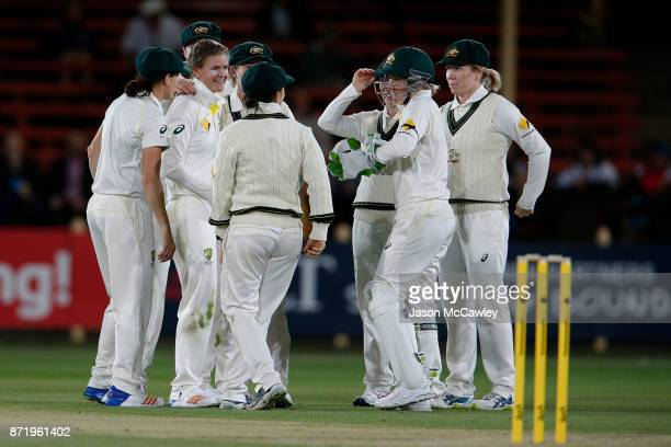 Jess Jonassen of Australia celebrates with team mates after dismissing Nat Sciver of England during the Women's Test match between Australia and...