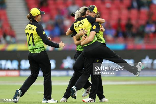 Jess Jonassen of Australia watches on as Annabel Sutherland of Australia celebrates with Ellyse Perry of Australia after taking the catch to dismiss...