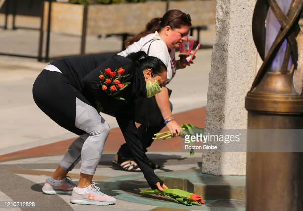 Jess Phifer left and Melanie DiVista lay down tulips at the Boston Marathon Bombing Memorial on One Boston Day the sevenyear anniversary of the...