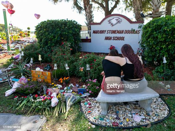 Jess Shanahan puts her arm around her friend, Lauryn Augustyne as they visit a makeshift memorial outside of Marjory Stoneman Douglas High School in...