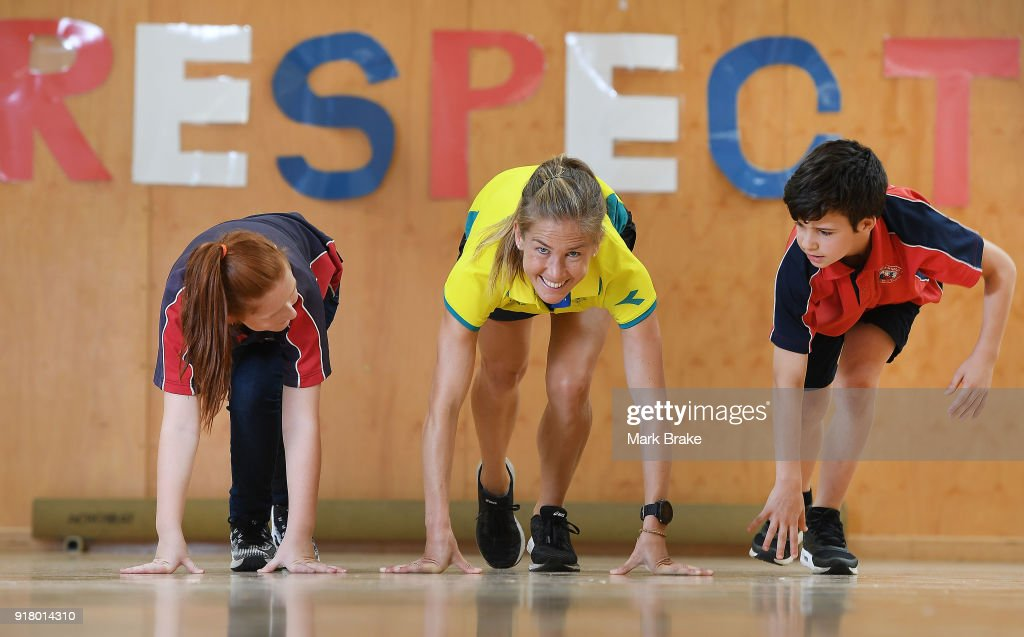 Jess Trengove poses for race start with students Caitlin Mitchell and Jamie Phillips during the Commonwealth Games Schools Assembly at Pennington Primary School on February 14, 2018 in Adelaide, Australia.