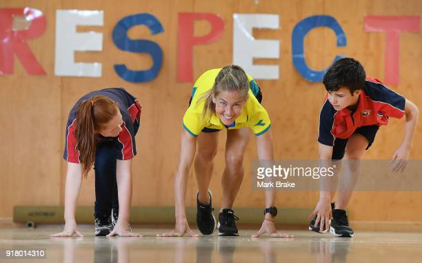 Jess Trengove poses for race start with students Caitlin Mitchell and Jamie Phillips during the Commonwealth Games Schools Assembly at Pennington...