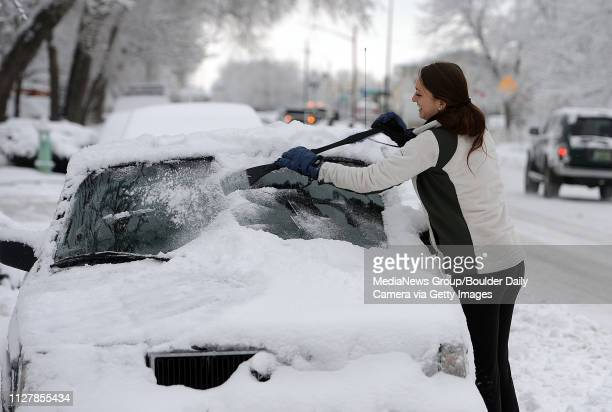 Jessa Wright scrapes the snow off her car on Spruce Street on Friday