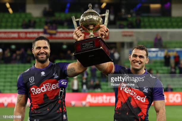 Jesse Bromwich of the Storm and Dale Finucane of the Storm holds aloft the Michael Moore trophy after winning the round seven NRL match between the...