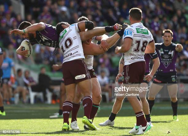 Jesse Bromwich of the Storm is lifted by Martin Taupau of the Sea Eagles during the round 21 NRL match between the Melbourne Storm and the Manly Sea...