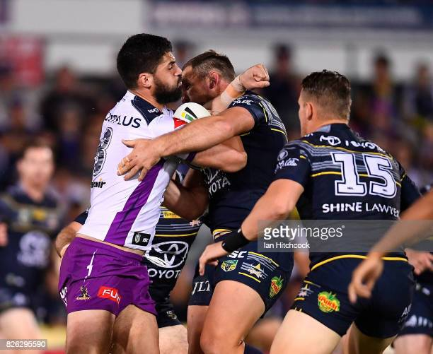 Jesse Bromwich of the Storm is tackled by Scott Bolton of the Cowboys during the round 22 NRL match between the North Queensland Cowboys and the...