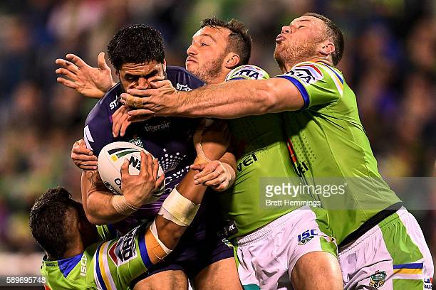 Jesse Bromwich of the Storm is tackled during the round 23 NRL match between the Canberra Raiders and the Melbourne Storm at GIO Stadium on August...