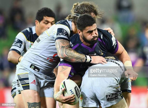 Jesse Bromwich of the Storm passes the ball whilst being tackled during the round 15 NRL match between the Melbourne Storm and the North Queensland...