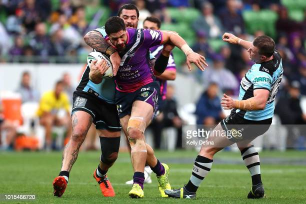 Jesse Bromwich of the Storm runs with the ball while being tackled by Sharks defense during the round 22 NRL match between the Melbourne Storm and...