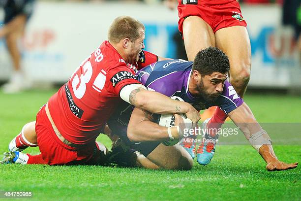 Jesse Bromwich of the Storm scores a try against Trent Merrin of the Dragons during the round 6 NRL match between the Melbourne Storm and the St...