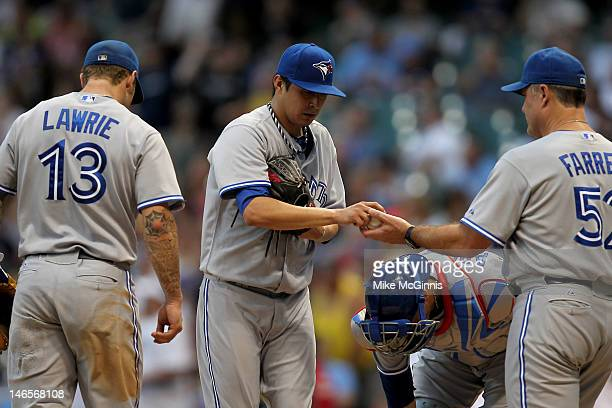 Jesse Chavez of the Toronto Blue Jays hands over the ball after getting pulled by Manager John Farrell in the bottom of the 3rd inning during the...