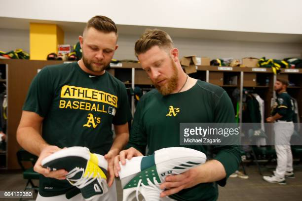 Jesse Hahn and Sean Doolittle of the Oakland Athletics check out their new shoes in the clubhouse prior to the game against the Texas Rangers at...