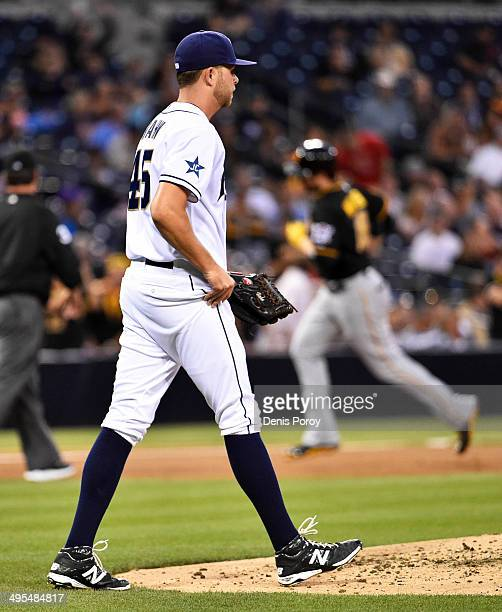 Jesse Hahn of the San Diego Padres walks back to the mound as Neil Walker of the Pittsburgh Pirates rounds the bases after hitting a tworun home run...