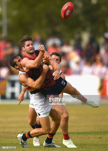 Jesse Hogan of the Demons handballs whilst being tackled by Richard Douglas of the Crows during the round 10 AFL match between the Melbourne Demons...