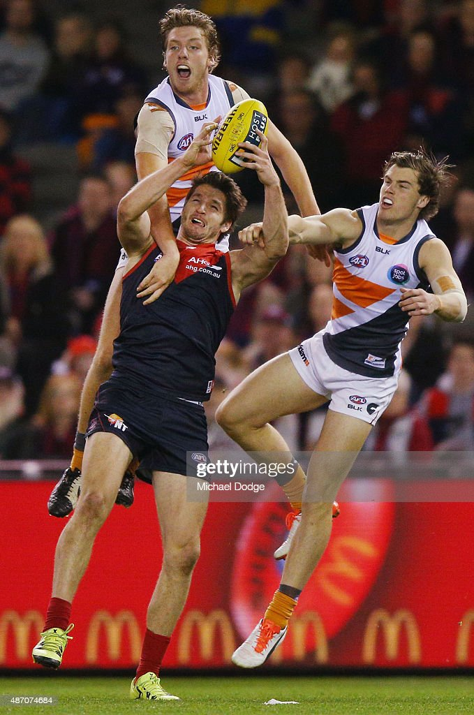 Jesse Hogan of the Demons marks the ball against Aidan Corr and Adam Tomlinson (R) during the round 23 AFL match between the Melbourne Demons and the Greater Western Sydney Giants at Etihad Stadium on September 6, 2015 in Melbourne, Australia.