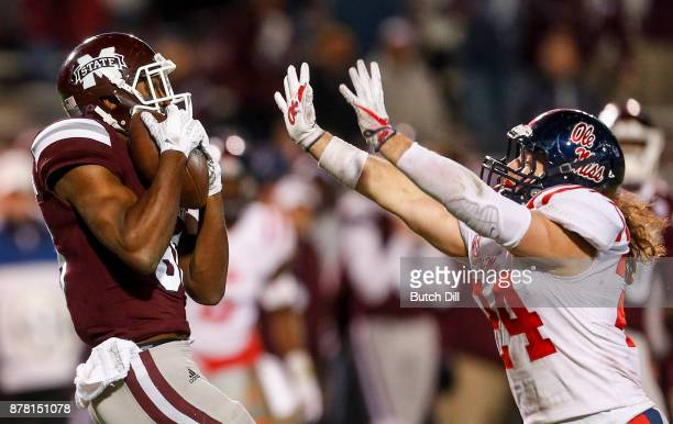 Jesse Jackson of the Mississippi State Bulldogs catches a pass over Tayler Polk of the Mississippi Rebels during the second half of an NCAA football...