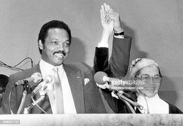 Jesse Jackson Sr and civil rights icon Rosa Parks raise their hands triumphantly during a speech 1965