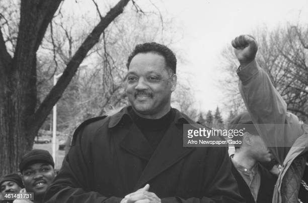 Jesse Jackson Sr stands with a crowd while an audience member gives a Black Power salute 1995