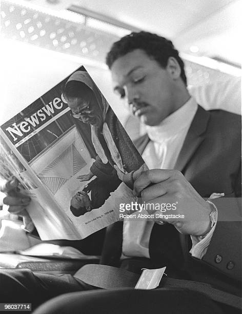 Jesse Jackson takes a moment to read a copy of Newsweek magazine with a cover showing a mourner passing by the body of the recently assassinated Dr...