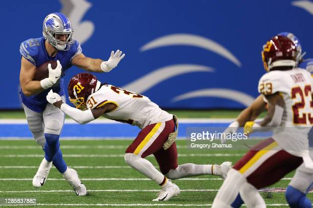 Jesse James of the Detroit Lions attempts to carry the ball following a catch against Kamren Curl of the Washington Football Team during their game...