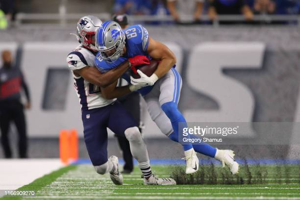 Jesse James of the Detroit Lions is tackled by Obi Melifonwu of the New England Patriots after a first quarter catch during a preseason game at Ford...