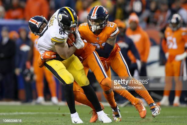 Jesse James of the Pittsburgh Steelers is tackled by Justin Simmons and Su'a Cravens of the Denver Broncos at Broncos Stadium at Mile High on...