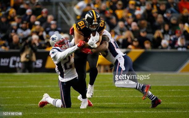 Jesse James of the Pittsburgh Steelers runs up field as Patrick Chung of the New England Patriots and J.C. Jackson attempt a tackle in the first half...