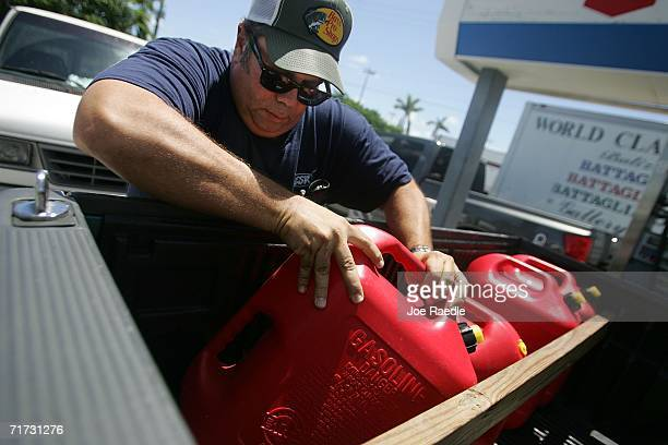 Jesse Jimenez works on filling extra tanks with gas for his home generator as he prepares for the approaching Tropical Storm Ernesto that is...
