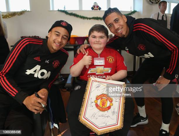 Jesse Lingard and Chris Smalling of Manchester United pose with Luke during the MU Foundation's Dream Day for fans with lifelimiting illnesses at Aon...