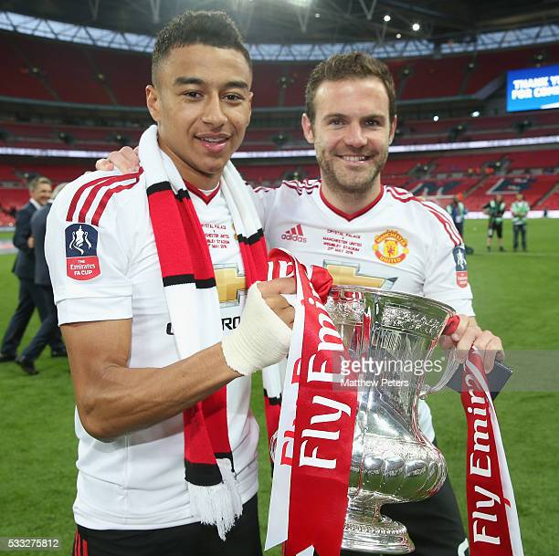 Jesse Lingard and Juan Mata of Manchester United celebrate with the FA Cup trophy after The Emirates FA Cup final match between Manchester United and...