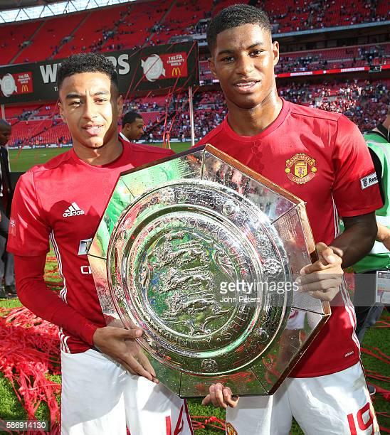 Jesse Lingard and Marcus Rashford of Manchester United pose with the Community Shield trophy after the FA Community Shield match between Leicester...