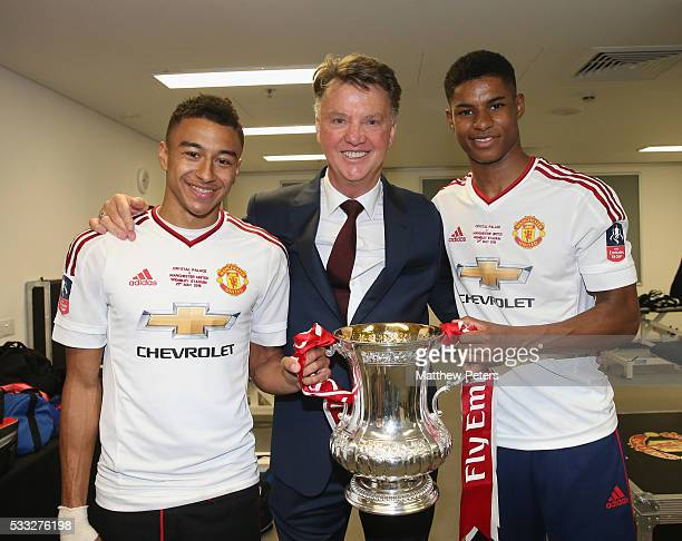Jesse Lingard Manager Louis van Gaal and Marcus Rashford of Manchester United celebrate in the dressing room with the FA Cup trophy after The...